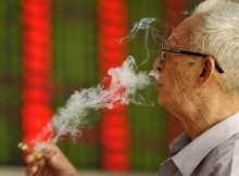 An investor smokes a cigarette in front of an electronic board showing stock information at a brokerage house in Fuyang, Anhui province, China, September 14, 2015. China stocks fell more than 3 percent on Monday morning as lingering concerns over the economy offset optimism that reform among state-owned enterprises (SOEs) would accelerate. REUTERS/Stringer CHINA OUT. NO COMMERCIAL OR EDITORIAL SALES IN CHINA  - RTSY62
