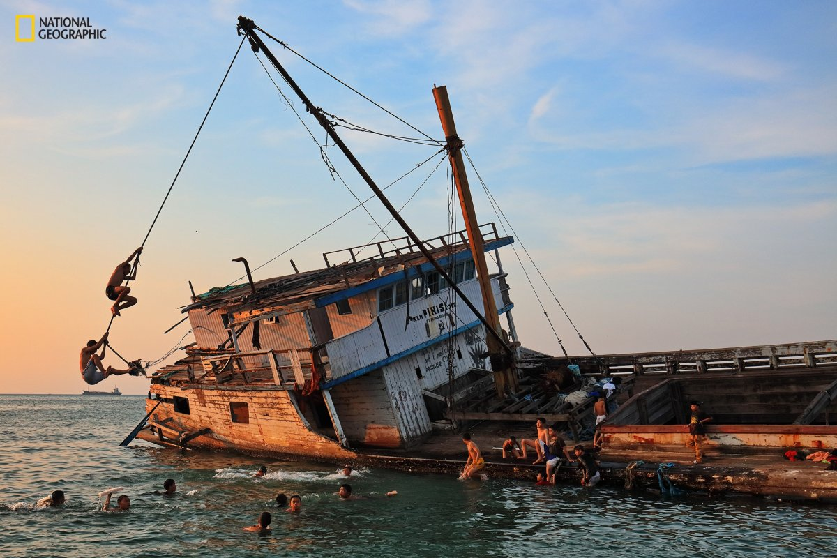 children-in-the-port-paotere-play-near-a-centuries-old-shipwrecked-wooden-boat-pinisi-which-once-explored-the-boundaries-ofmakassar-in-south-sulawesi-indonesia