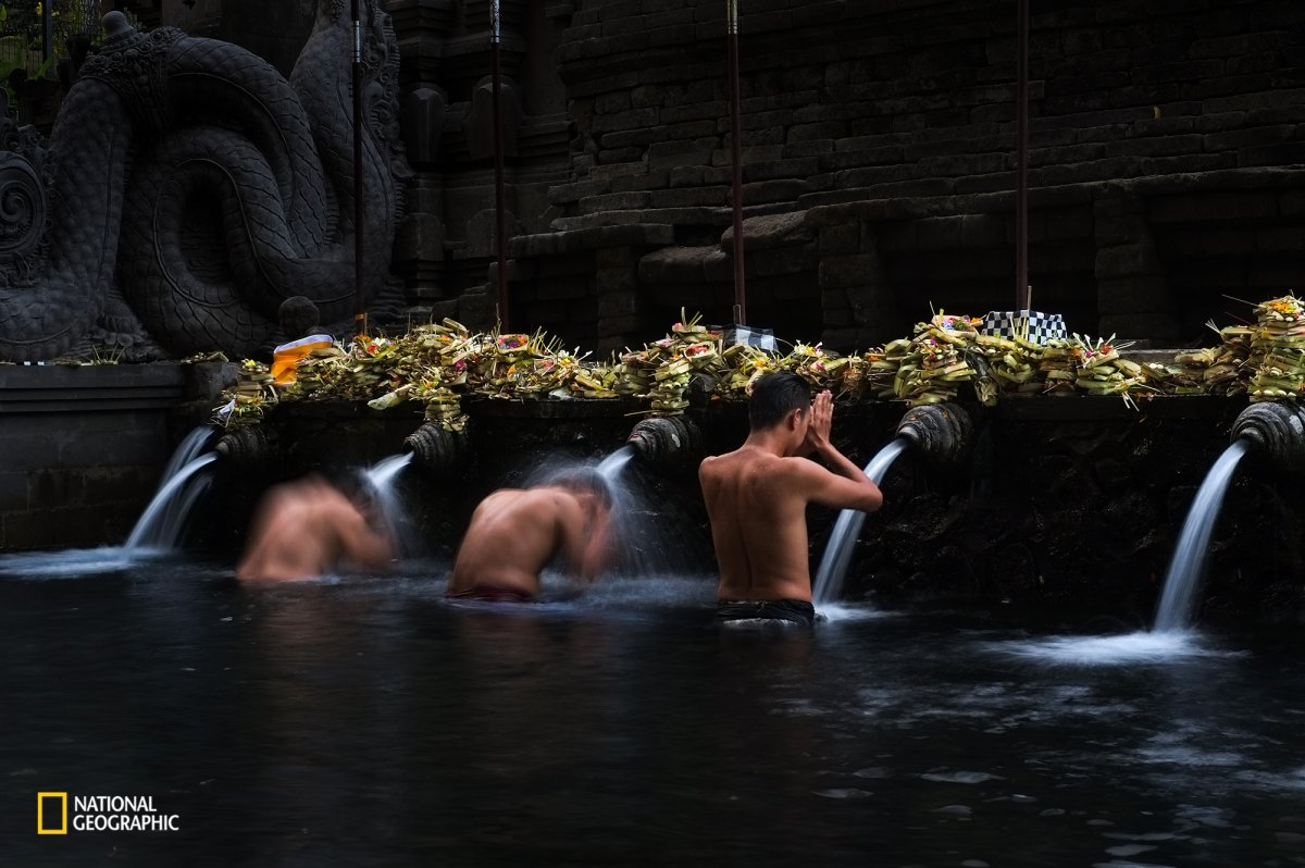 men-take-part-in-a-bathing-ritual-in-the-tirta-empul-temple-in-bali-the-temples-fresh-spring-water-is-believed-to-be-holy-water-that-purifies-the-body-and-soul