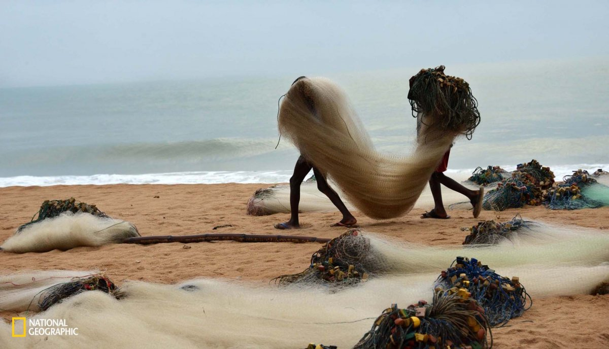 two-young-anglers-in-greater-accra-ghana-carry-fishing-nets-to-their-boat