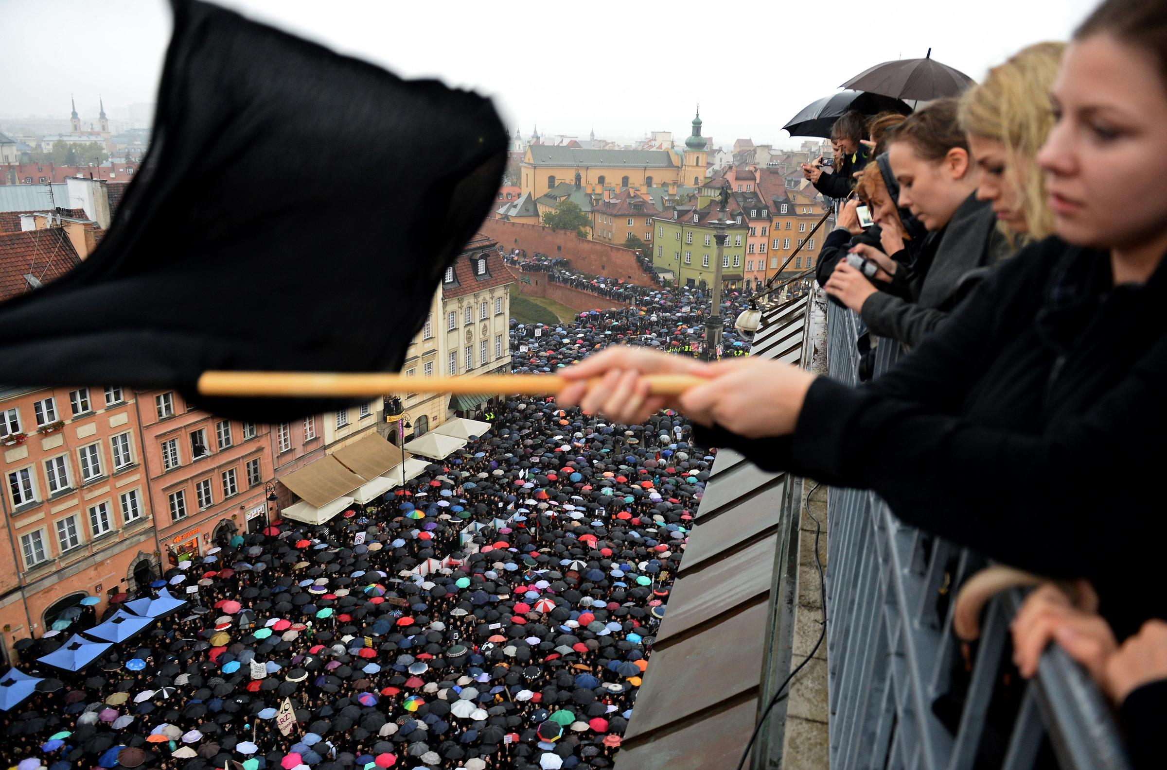 A girl waves a black flag on Monday as people in Warsaw take part in a nationwide strike and demonstration to protest against a legislative proposal for a total ban of abortionin Poland