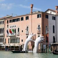 Venezia, due mani giganti spuntano da un canale per sostenere il peso del cambiamento climatico